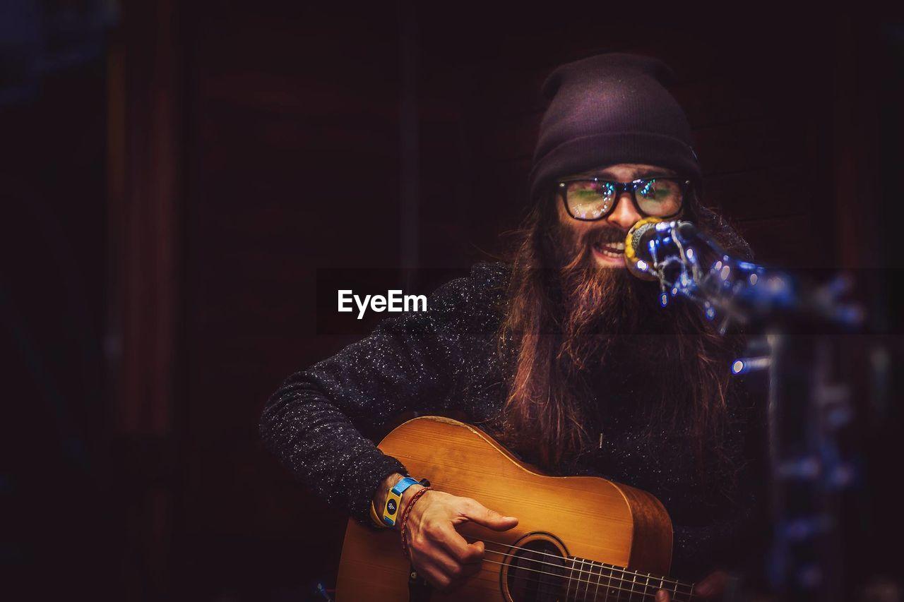 Hipster singing while playing guitar