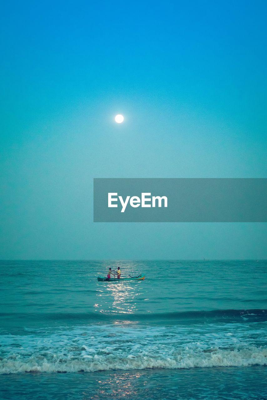 Men in boat on sea against sky at dawn
