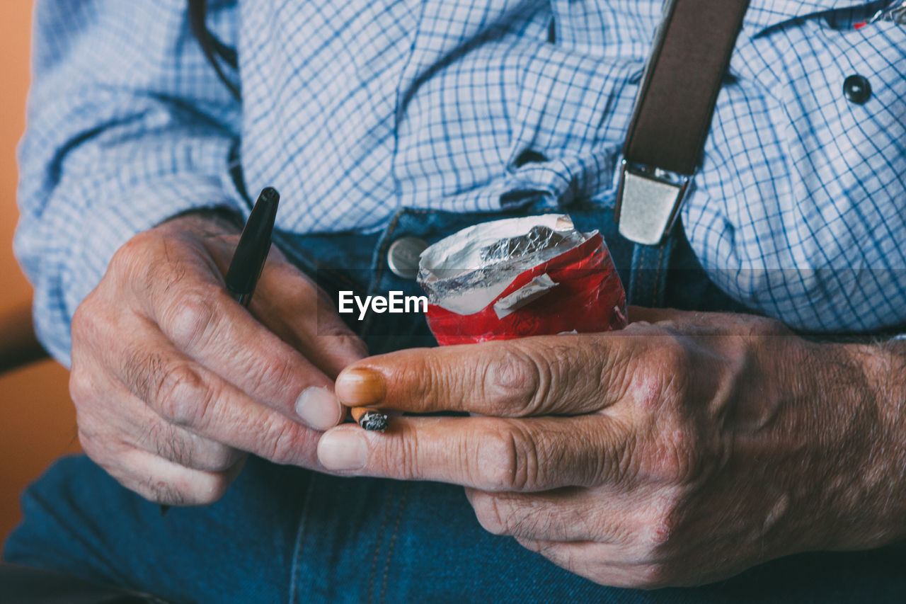 Midsection Of Man Holding Cigarette Butt