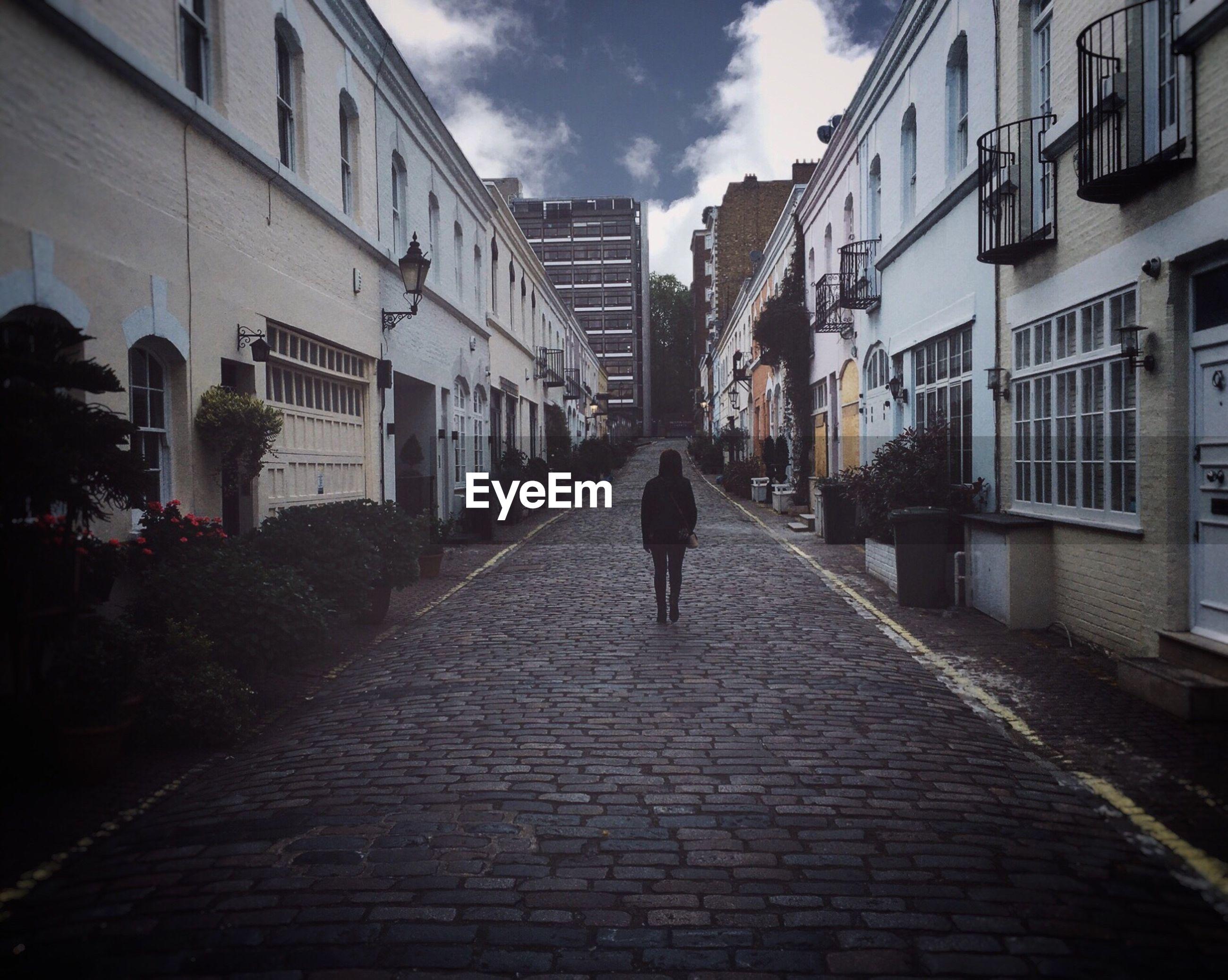 Man walking on alley amidst street