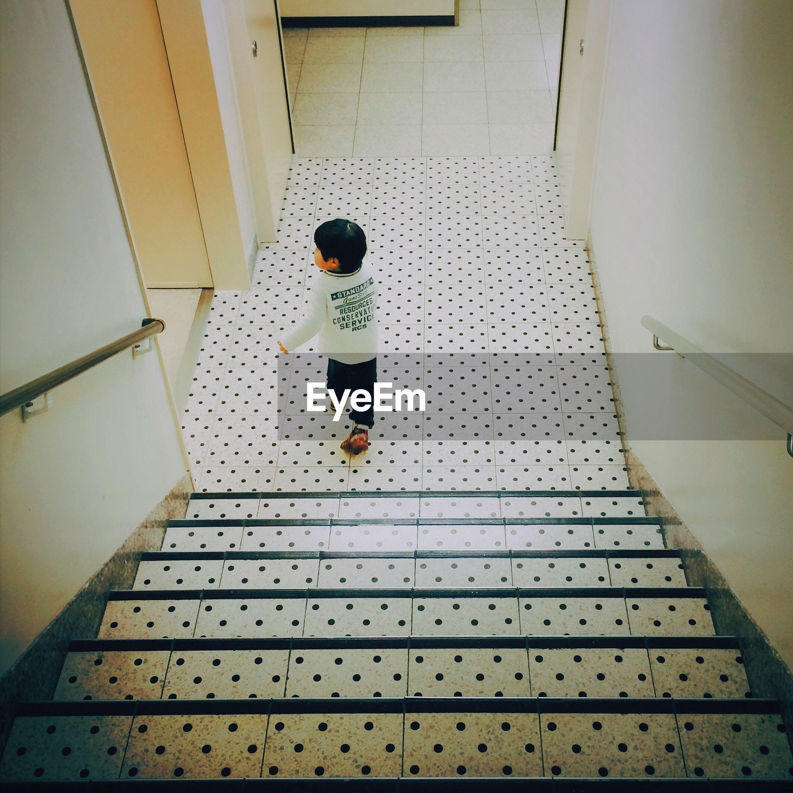 Full length rear view of child walking on corridor