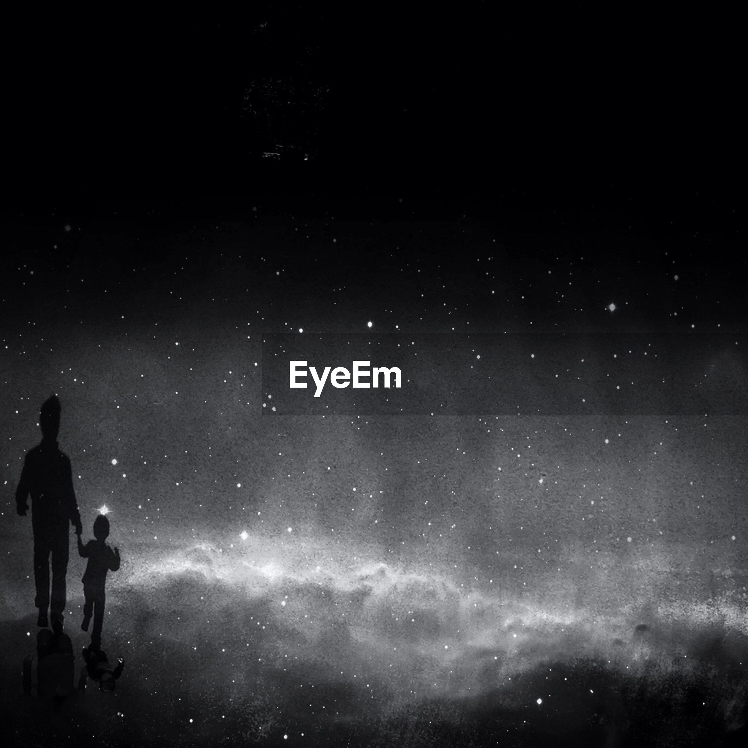 Double exposure of father and son walking on star field