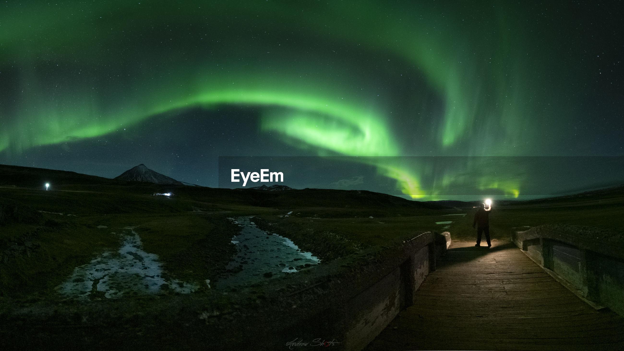 Man with flashlight standing under sky at night