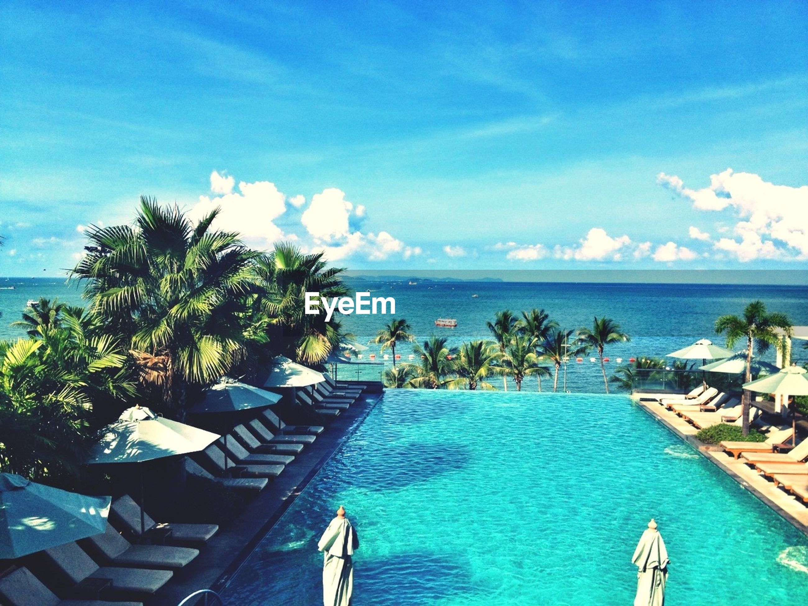 sea, water, horizon over water, blue, palm tree, sky, tranquil scene, scenics, beauty in nature, tranquility, tree, beach, nature, tourist resort, cloud - sky, turquoise colored, idyllic, swimming pool, cloud, ocean