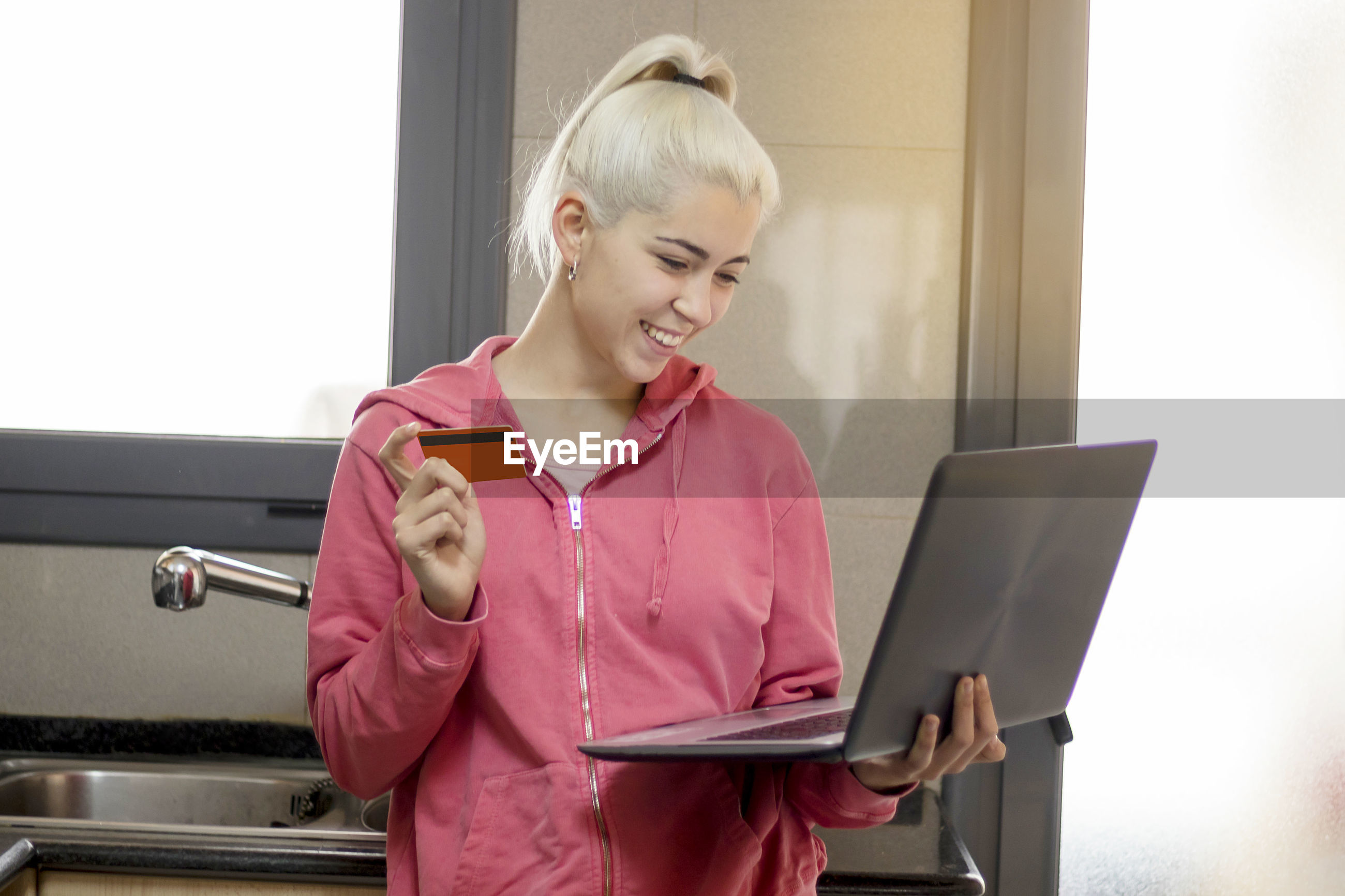 Smiling young woman holding credit card while using laptop at home