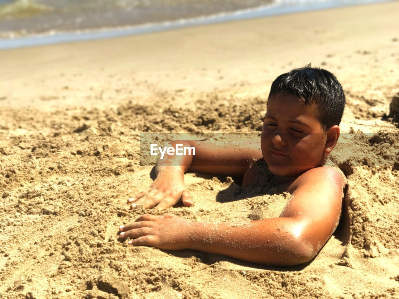 sand, beach, childhood, boys, one person, shirtless, real people, shore, outdoors, water, day, focus on foreground, elementary age, sunlight, leisure activity, vacations, sea, nature, lifestyles, sand pail and shovel, beauty in nature, one boy only, close-up