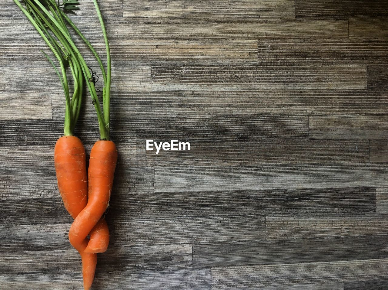 food and drink, food, wood - material, vegetable, healthy eating, wellbeing, freshness, table, still life, root vegetable, directly above, carrot, no people, indoors, high angle view, close-up, raw food, green color, orange color, plant part