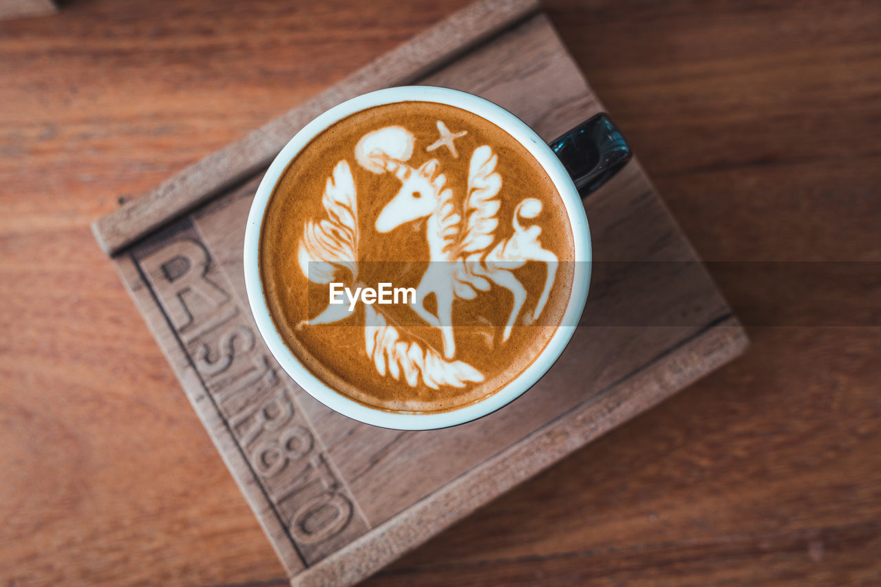 food and drink, coffee, coffee - drink, frothy drink, refreshment, cup, drink, table, mug, coffee cup, indoors, froth art, creativity, wood - material, latte, high angle view, no people, close-up, hot drink, still life, crockery