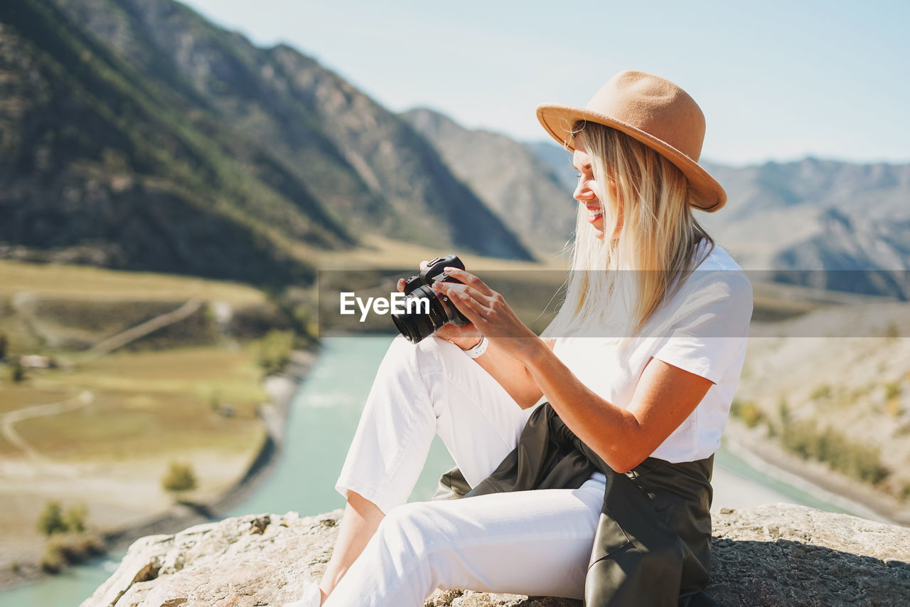 Beautiful smiling blone young woman traveler in felt hat with photo camera, trip to mountains