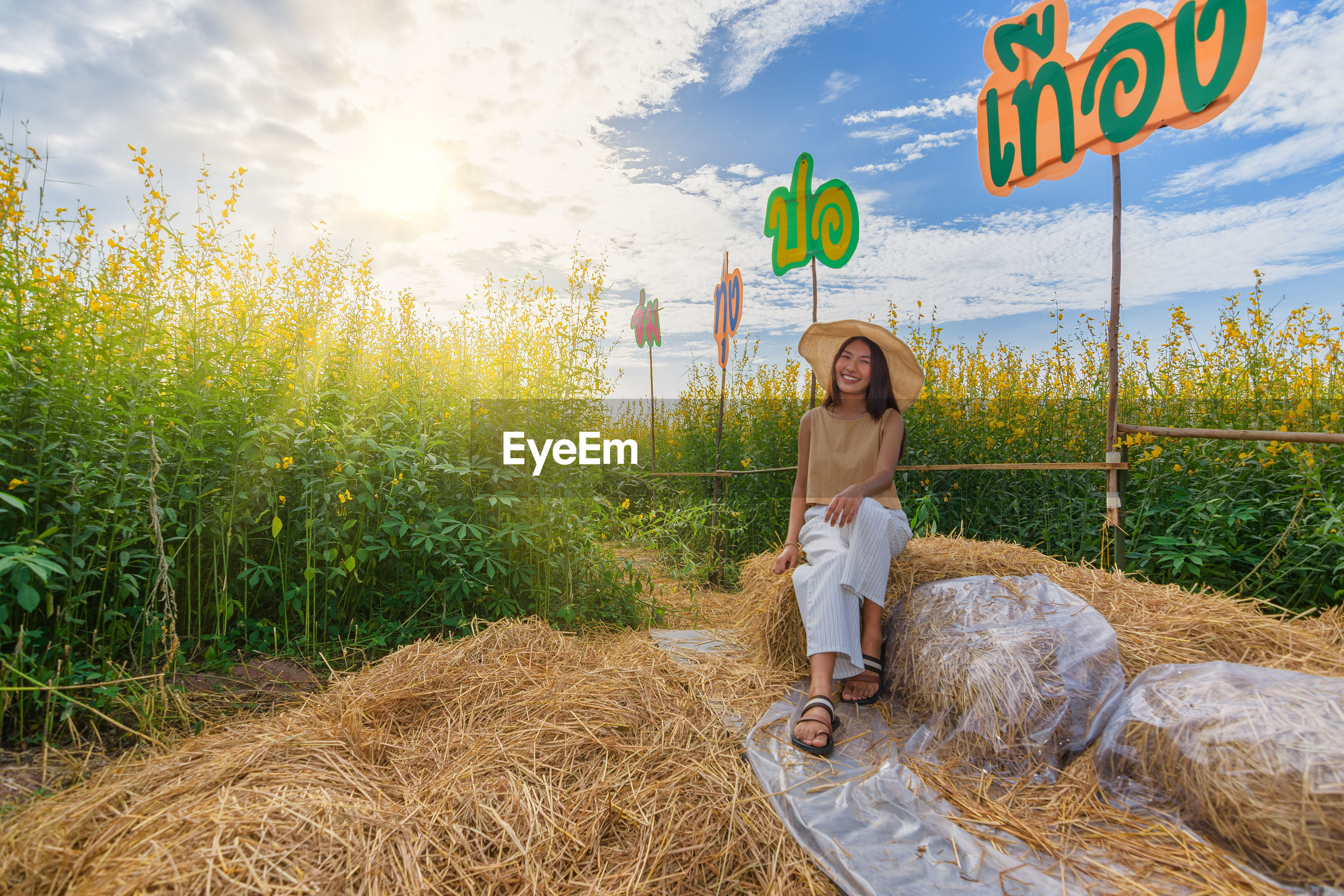 Full length of woman sitting on hay bale against text and sky
