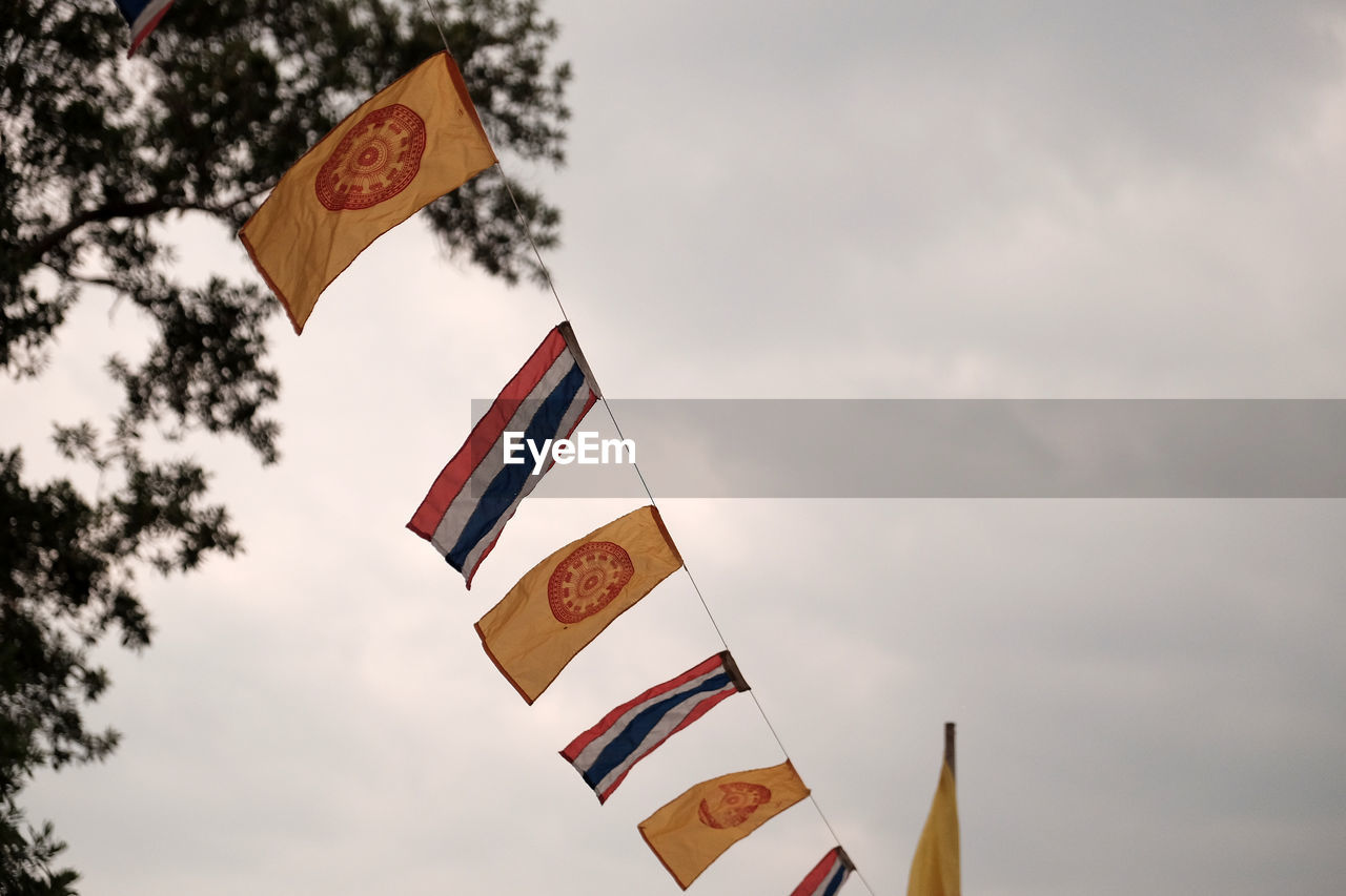 flag, sky, patriotism, cloud - sky, nature, no people, low angle view, communication, day, text, pride, outdoors, focus on foreground, symbol, emotion, environment, wind, tree, multi colored, national icon