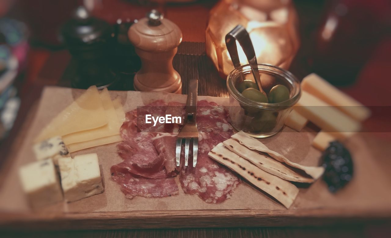 food and drink, indoors, food, freshness, table, meat, cutting board, drink, close-up, real people, human hand, high angle view, selective focus, still life, hand, leisure activity, refreshment, human body part, glass - material, preparation, glass