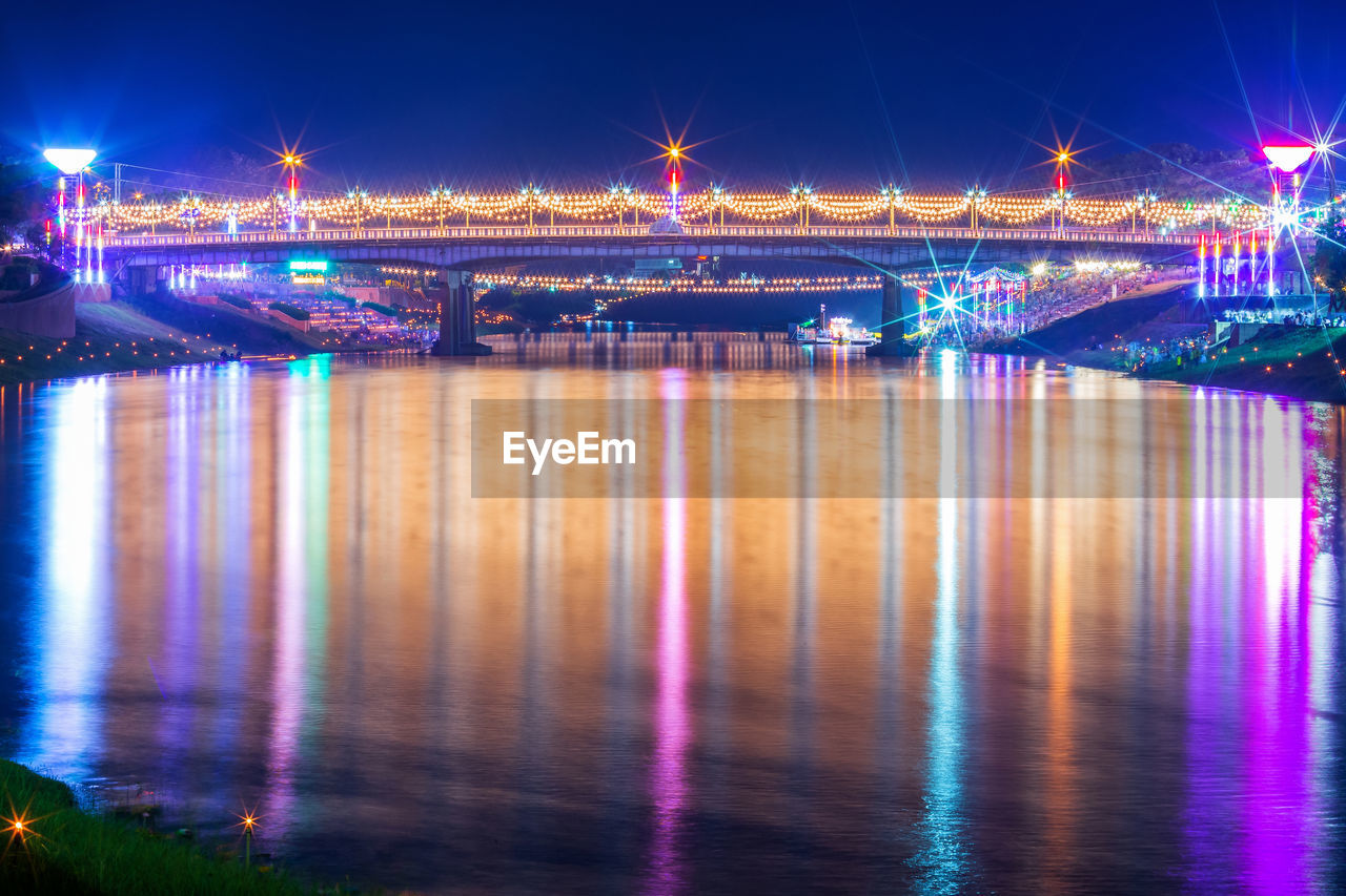 illuminated, reflection, architecture, water, night, built structure, transportation, city, river, waterfront, connection, no people, bridge, bridge - man made structure, long exposure, building exterior, lighting equipment, nature, multi colored, light