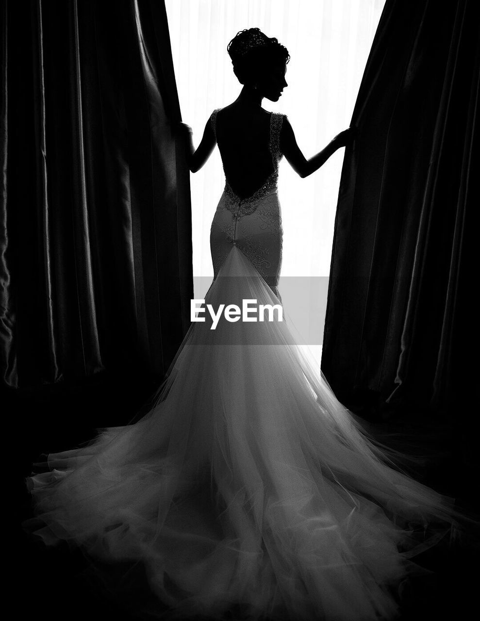 Rear view of fashion model in wedding dress while holding curtains