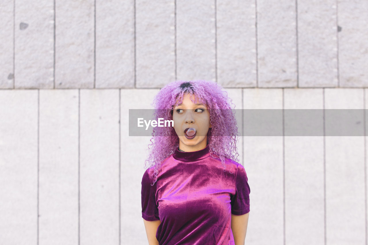 Woman with purple hair blowing bubble gum standing against wall