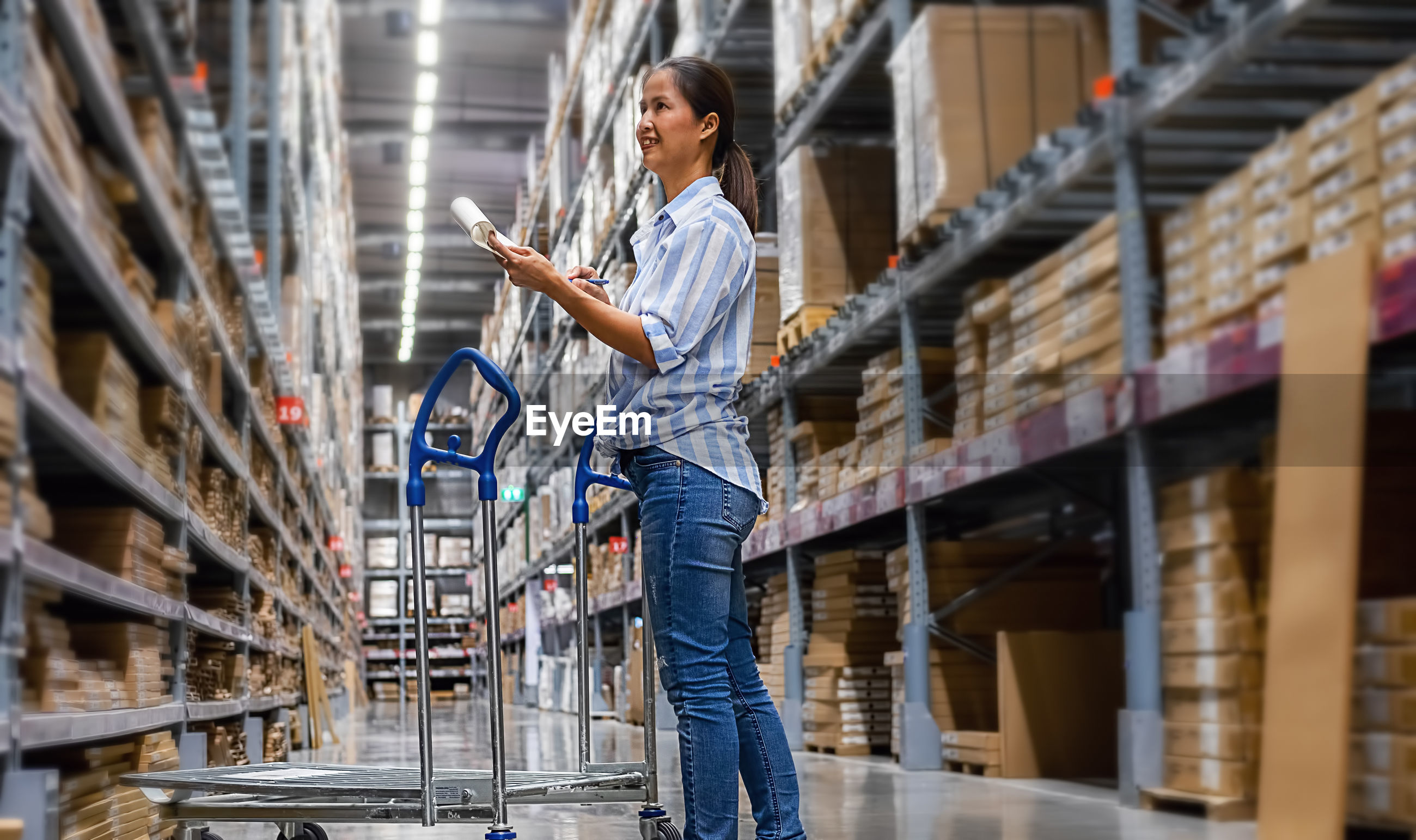Entrepreneur writing while standing in warehouse
