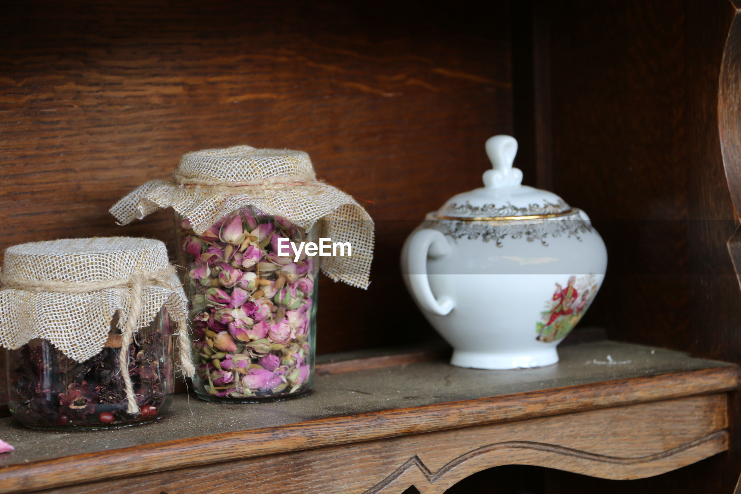 Close-up of flowers in jars on shelf