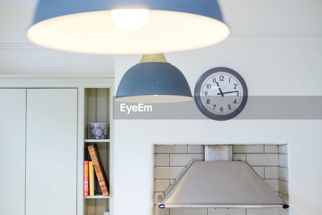 LOW ANGLE VIEW OF ILLUMINATED PENDANT LIGHTS ON WALL