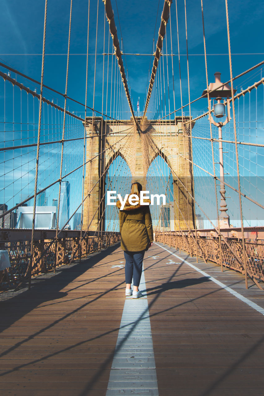Rear View Of Woman Walking On Brooklyn Bridge
