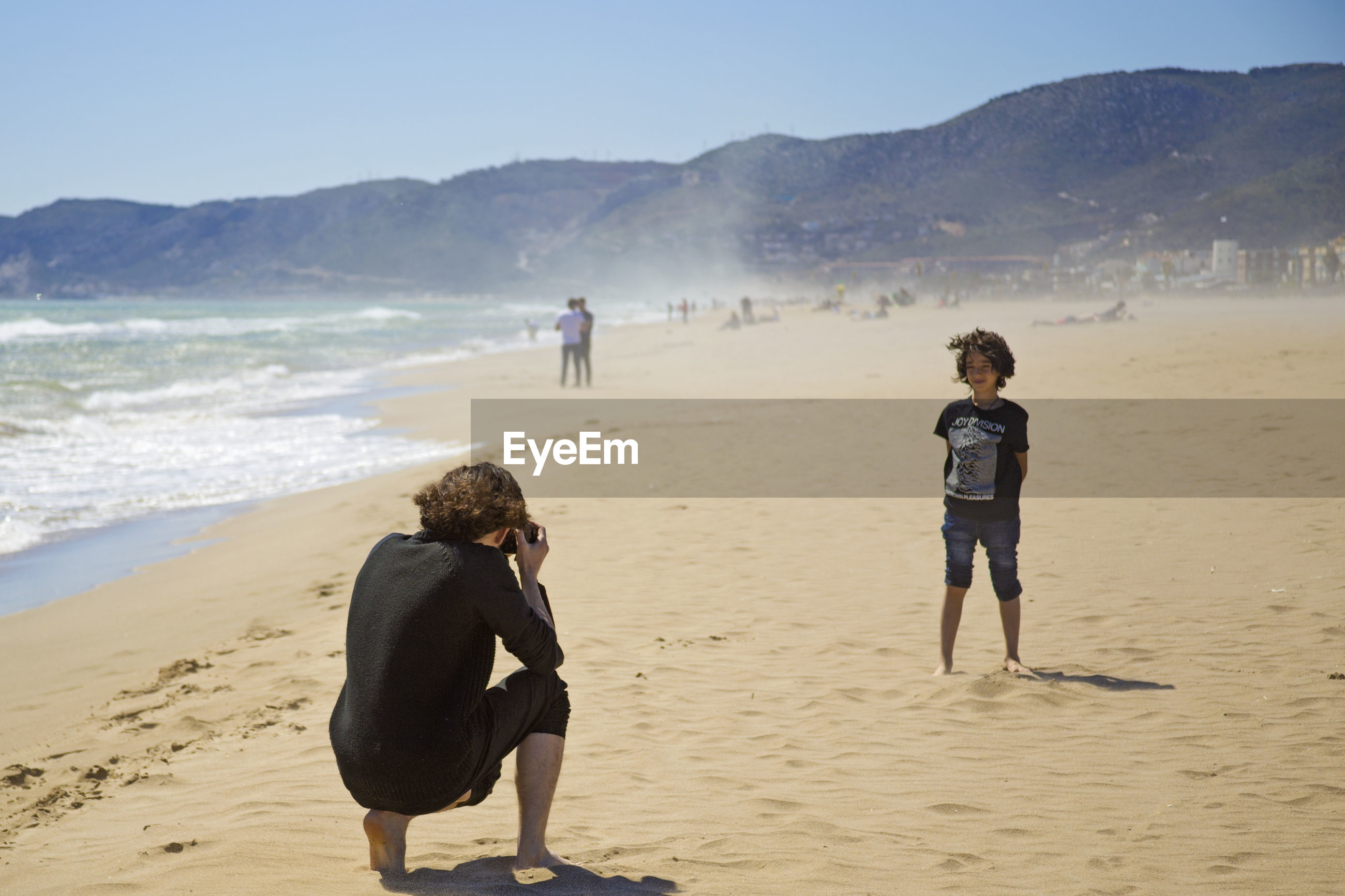 Rear view of woman photographing son at beach