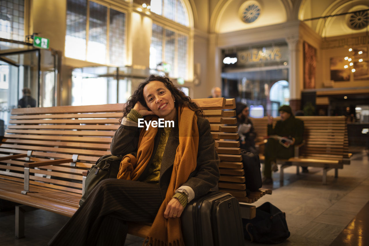 PORTRAIT OF A SMILING YOUNG WOMAN SITTING ON SEAT IN SHOPPING MALL