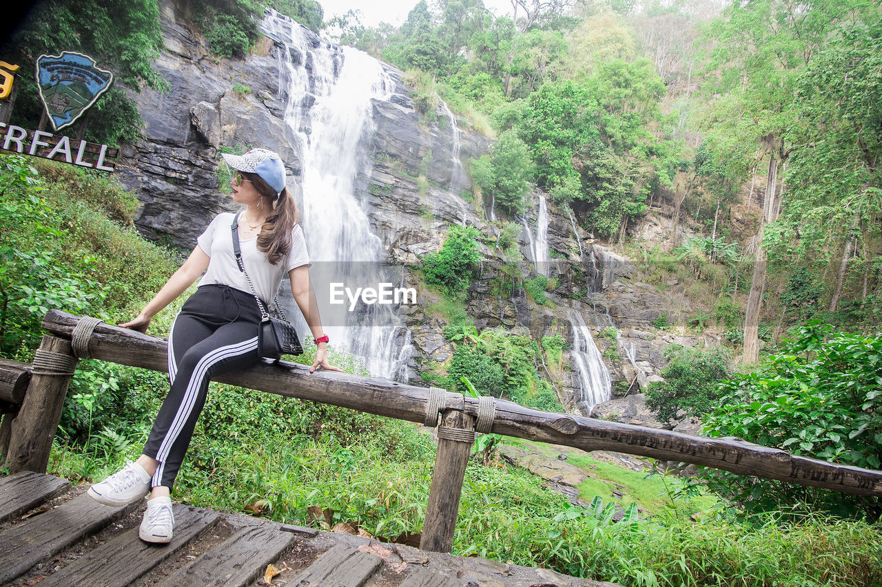 full length, one person, real people, lifestyles, plant, sitting, tree, young women, young adult, leisure activity, forest, casual clothing, nature, waterfall, beauty in nature, land, women, scenics - nature, green color, outdoors, flowing water, hairstyle
