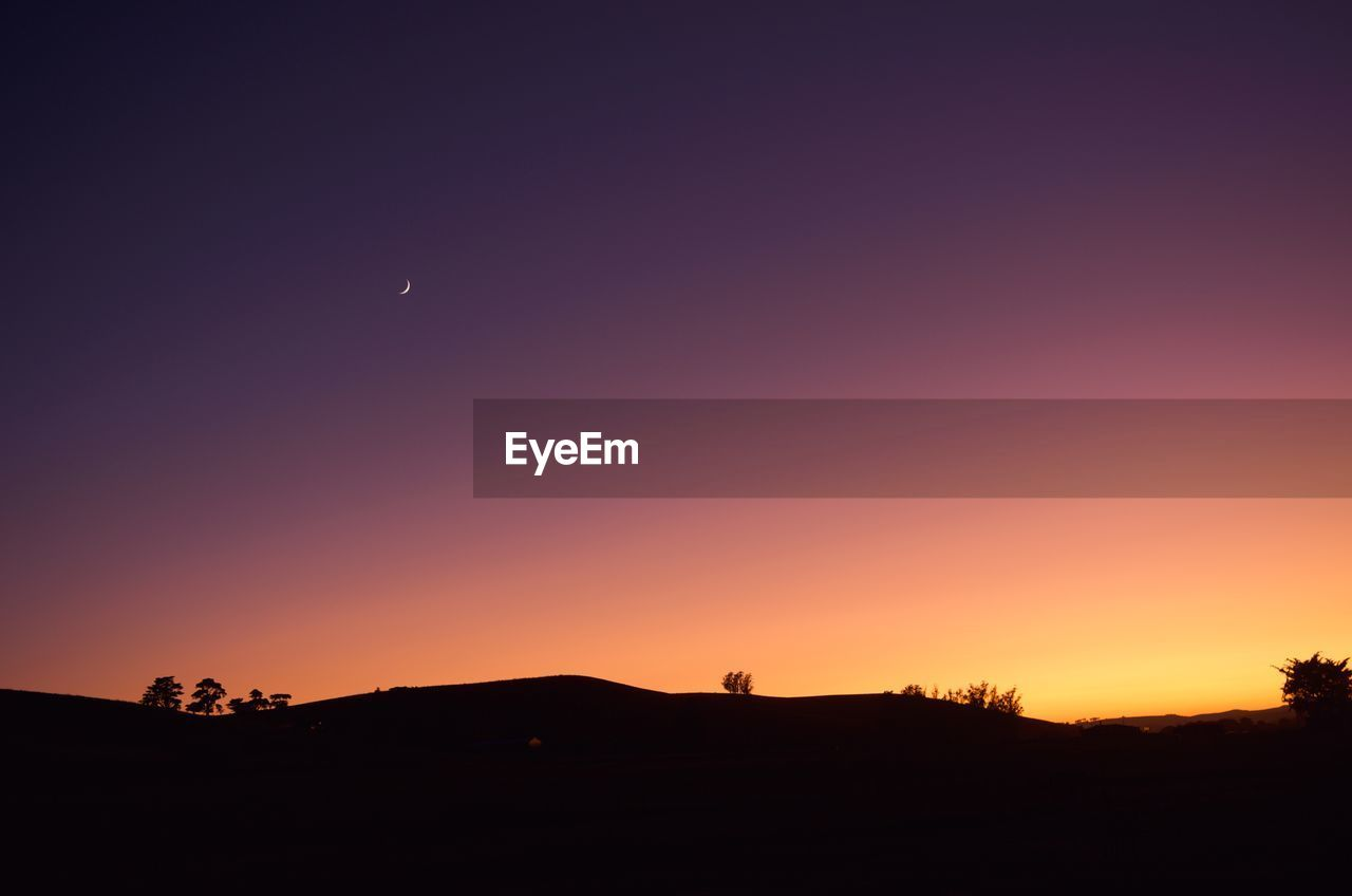 sky, sunset, silhouette, beauty in nature, scenics - nature, orange color, tranquility, copy space, tranquil scene, moon, landscape, environment, nature, idyllic, non-urban scene, clear sky, crescent, no people, land, space, outdoors, astronomy