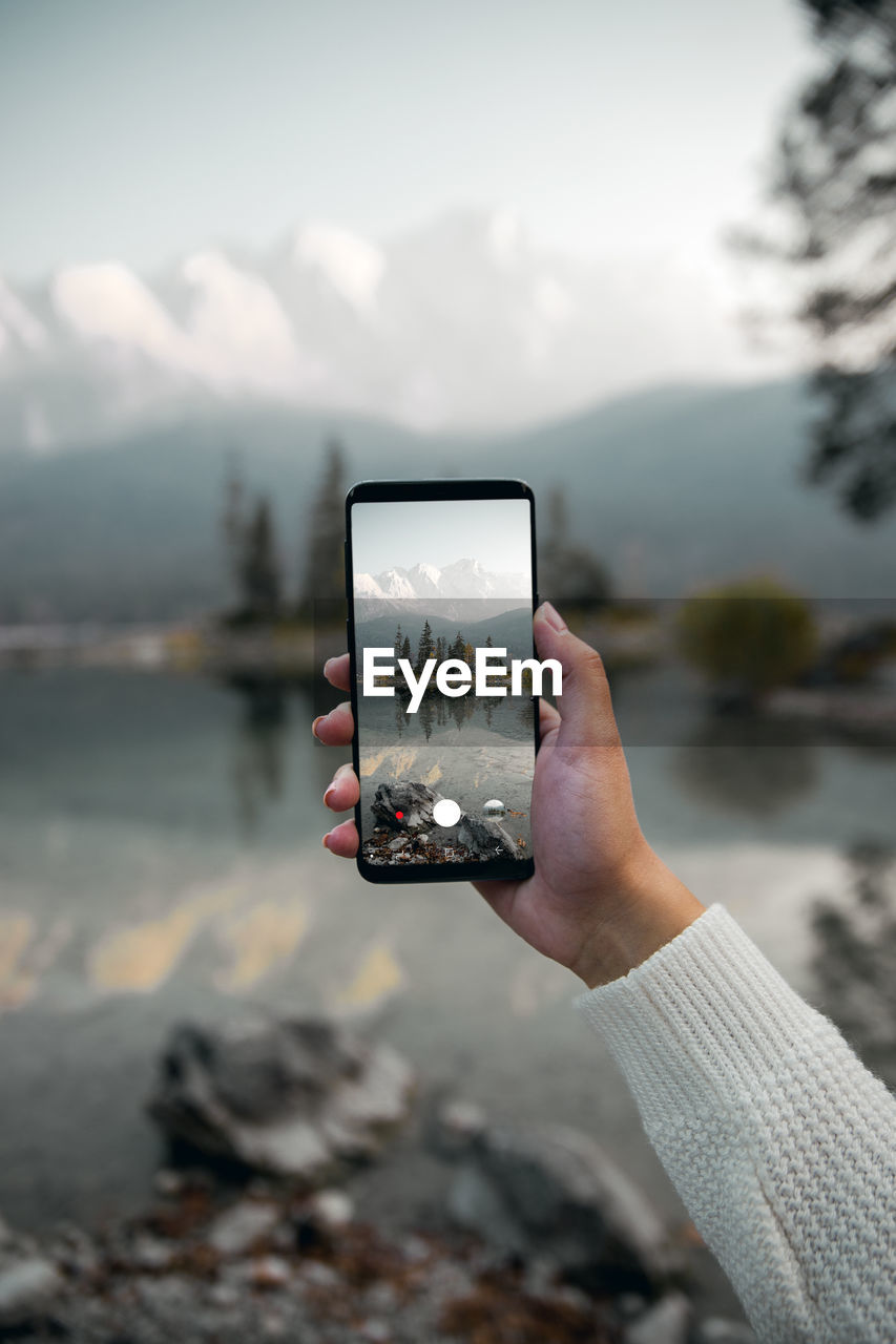 human hand, hand, holding, one person, technology, wireless technology, photography themes, focus on foreground, photographing, real people, leisure activity, human body part, communication, nature, portable information device, lifestyles, smart phone, unrecognizable person, activity, mountain, outdoors