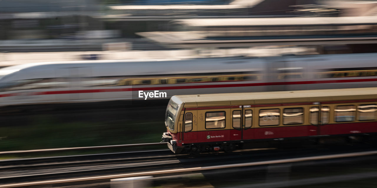motion, mode of transportation, transportation, speed, blurred motion, rail transportation, public transportation, train, land vehicle, on the move, train - vehicle, architecture, no people, travel, outdoors, city, red, railroad track, railroad station, day, track, subway train, railroad car