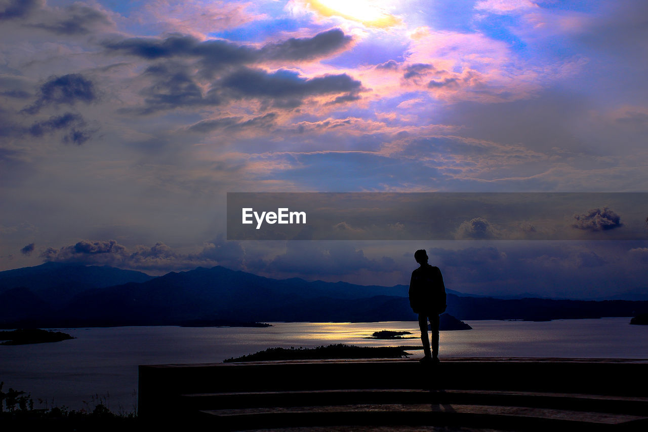 cloud - sky, sky, one person, sunset, real people, beauty in nature, silhouette, scenics - nature, water, full length, nature, lifestyles, rear view, standing, tranquility, tranquil scene, leisure activity, mountain, outdoors, looking at view