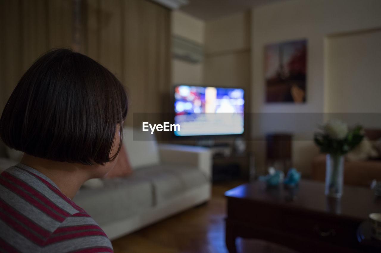 Close-Up Of Girl Watching Tv At Home