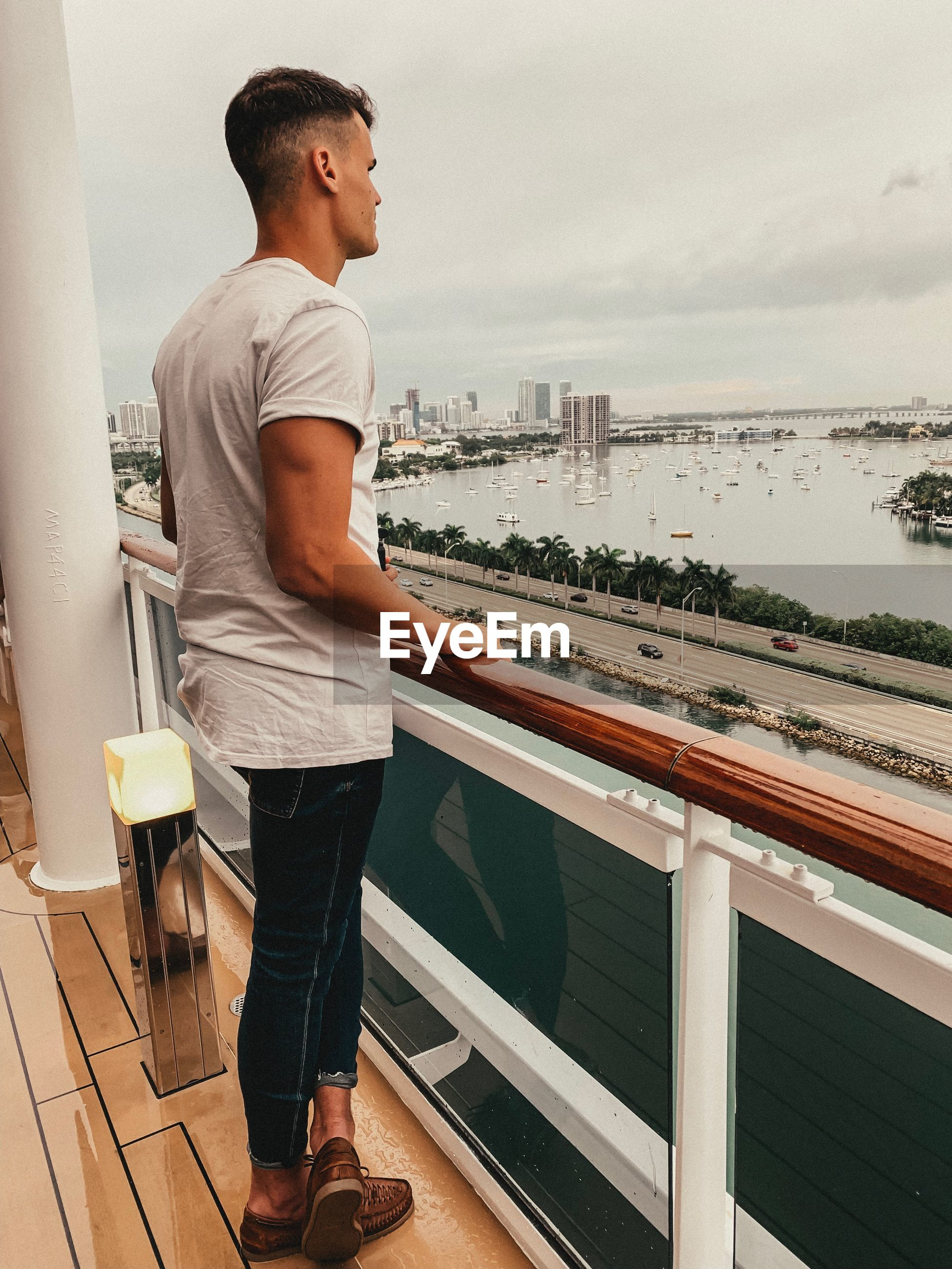 Side view of young man looking at sea while standing in balcony