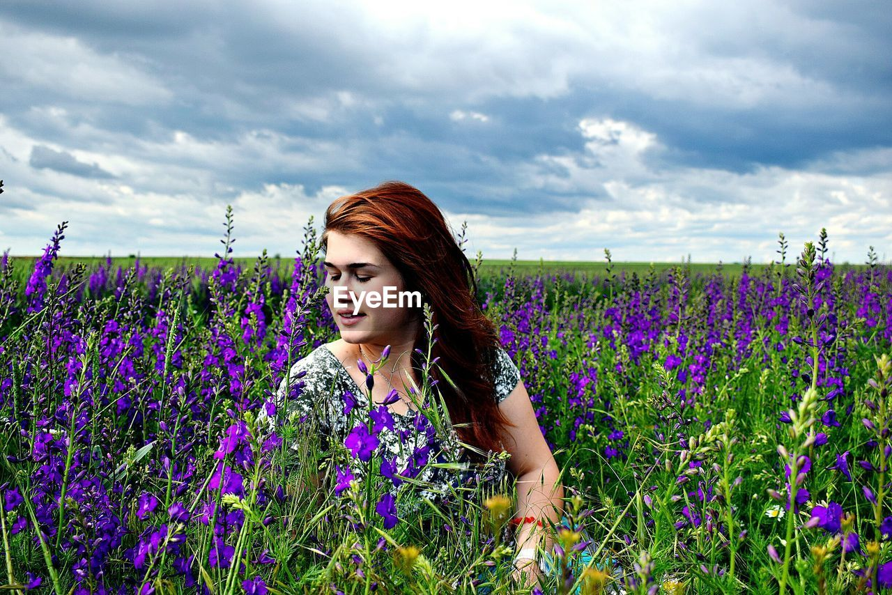 Beautiful Young Woman With Flowers On Field Against Sky