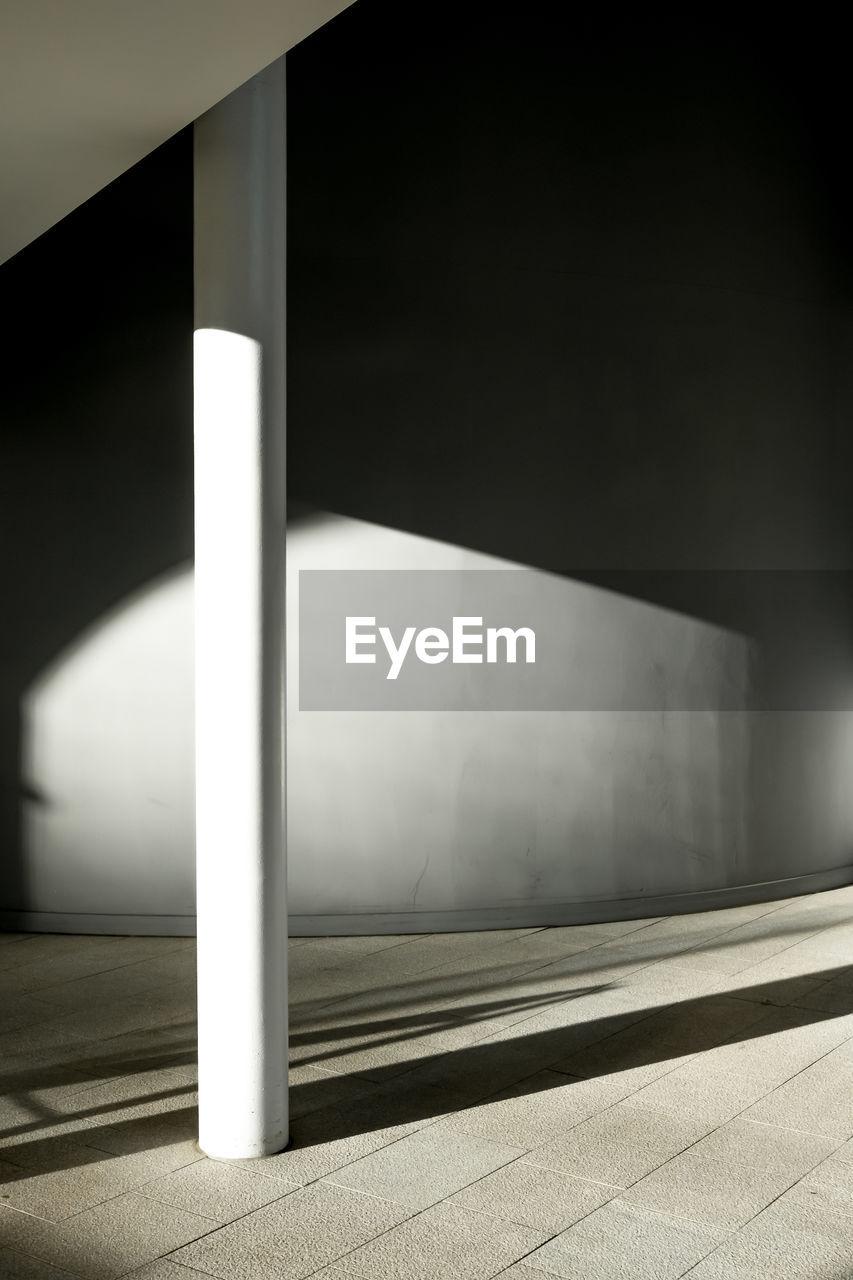 Sunlight falling on empty corridor by building