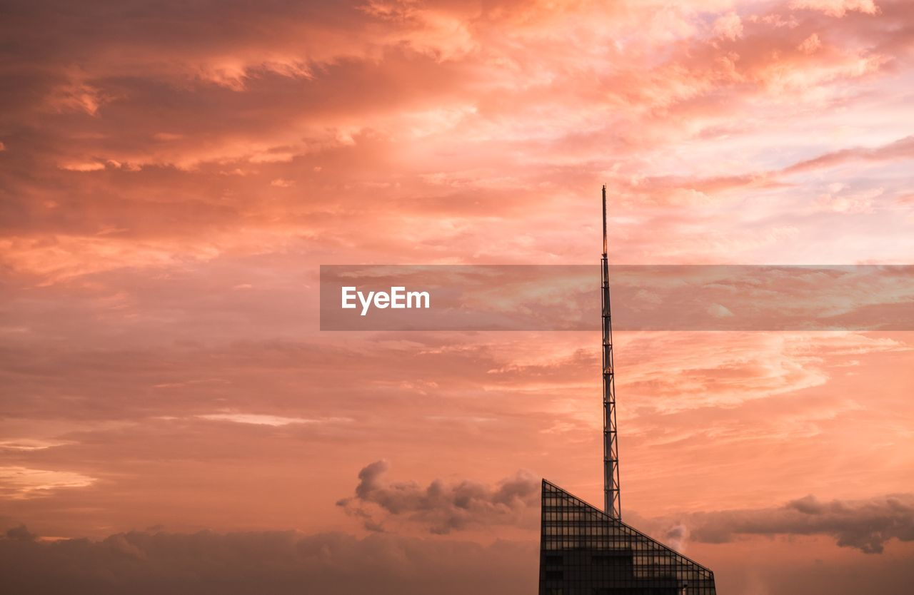 High section of modern building against sky during sunset