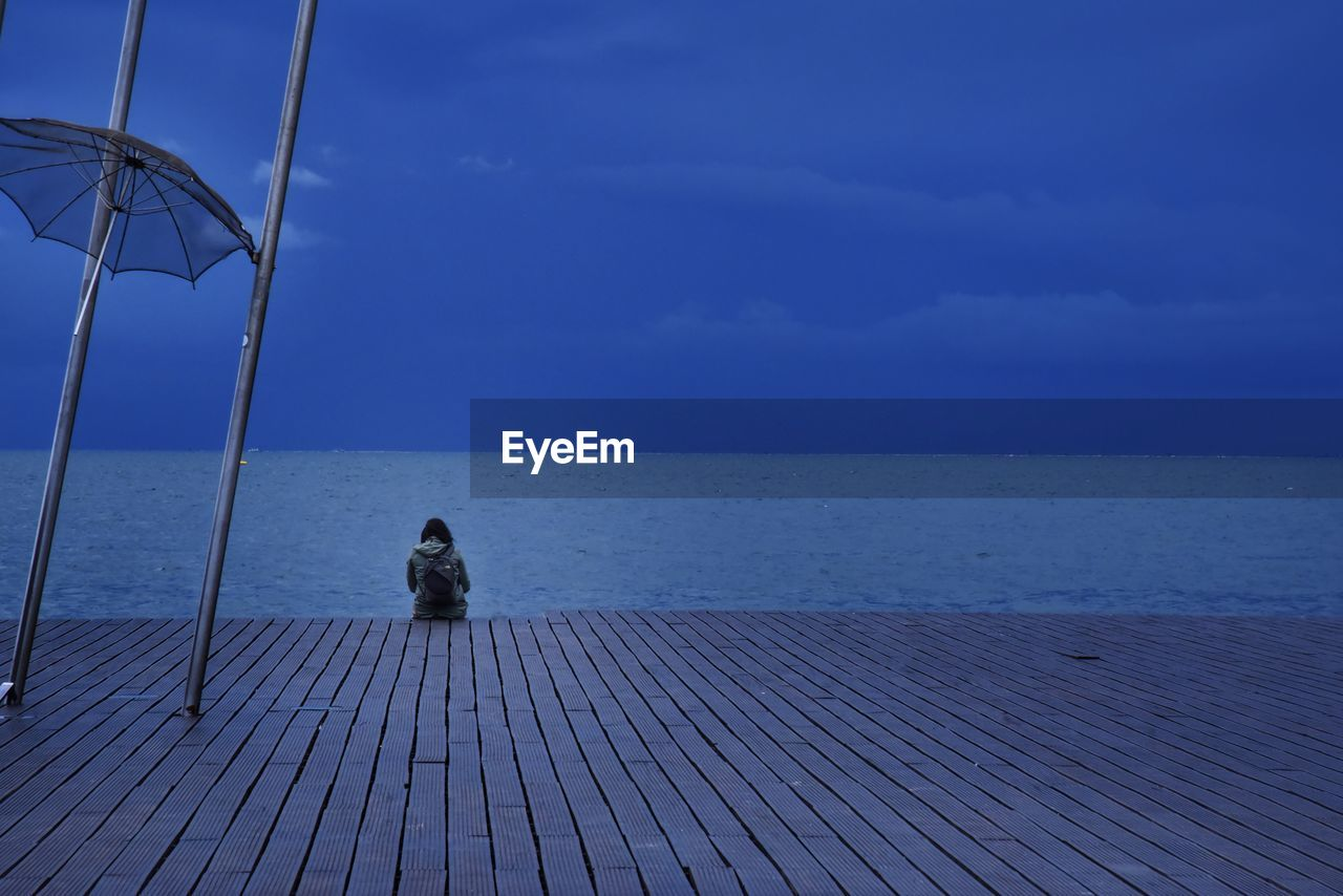 sky, horizon over water, horizon, sea, water, sitting, nature, scenics - nature, blue, cloud - sky, tranquility, beauty in nature, tranquil scene, day, rear view, pier, relaxation, wood - material, one person