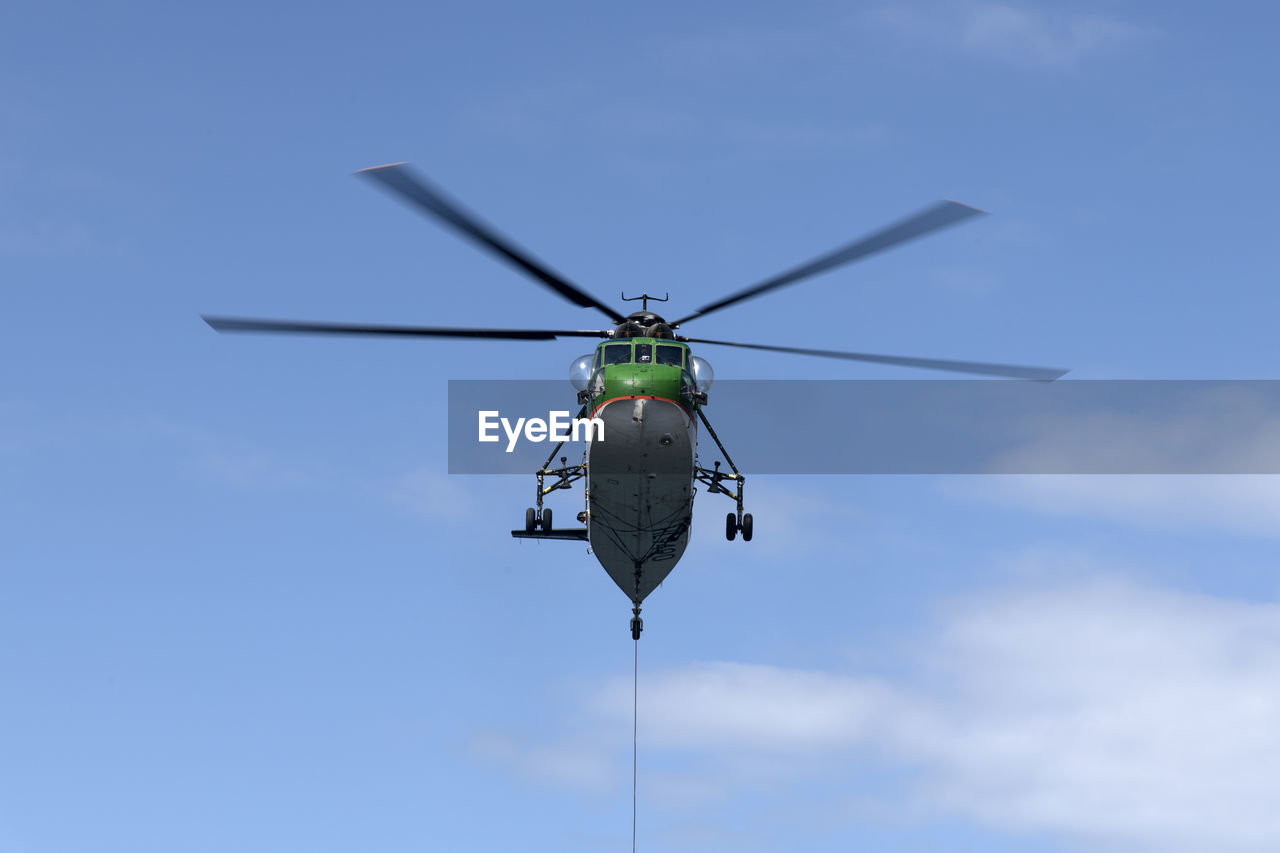 Low angle view of helicopter flying against blue sky