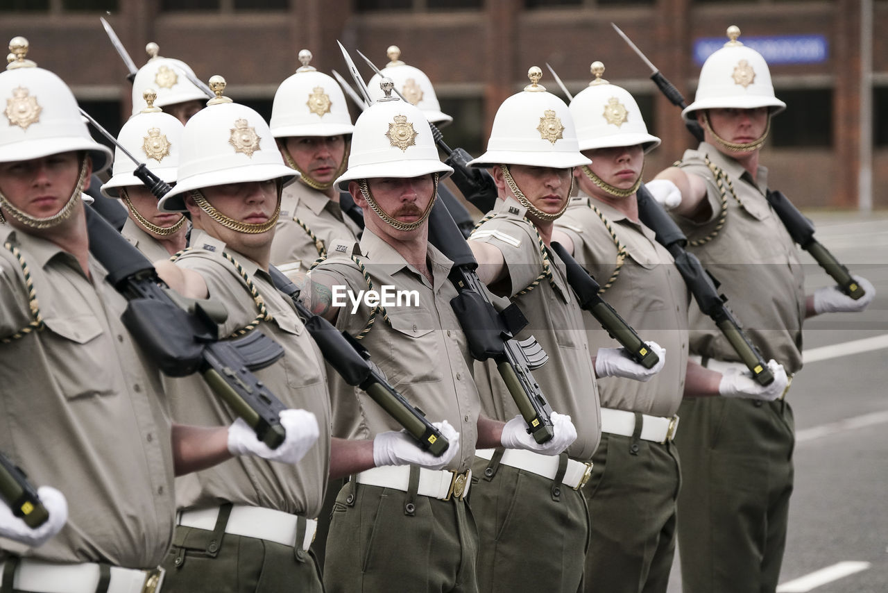 uniform, armed forces, military, government, army soldier, military uniform, clothing, military parade, group of people, army, weapon, security, headwear, teamwork, real people, day, people, army helmet, protection, parade, responsibility, marching