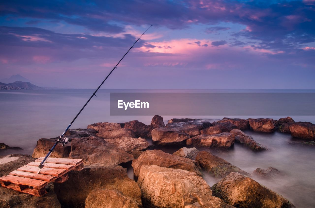 Fishing Rod On Shore Against Cloudy Sky At Sunset