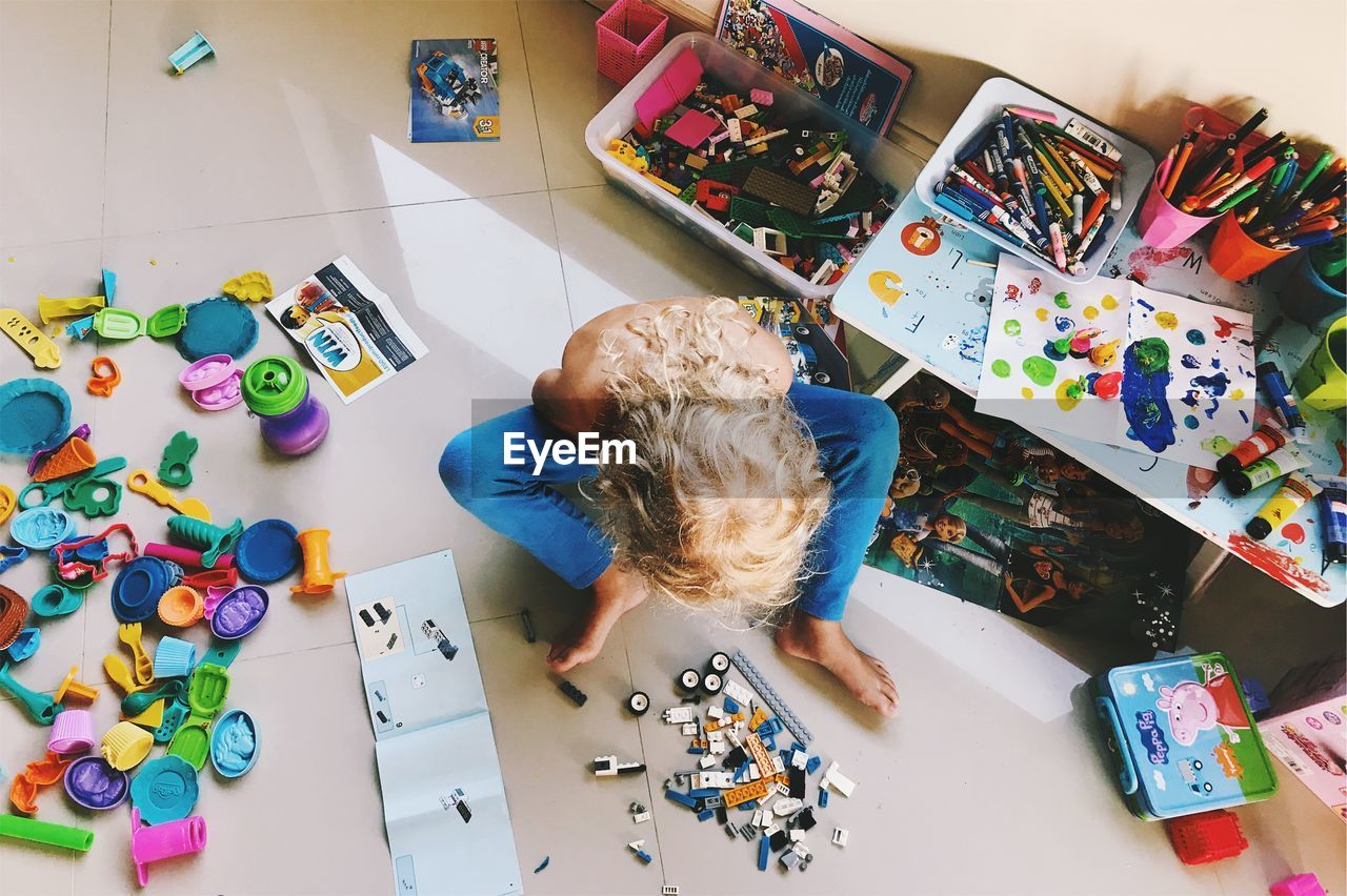 High Angle View Of Girl Playing With Toys At Home