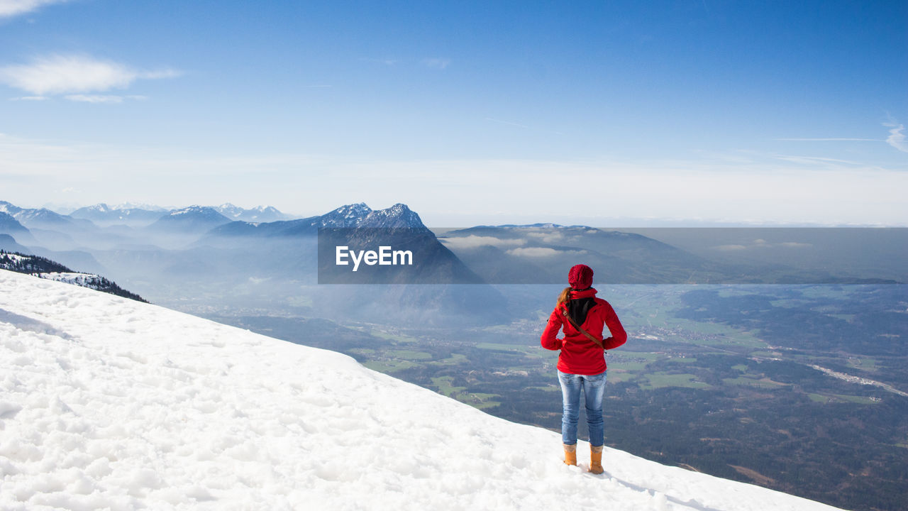 Rear view of young woman standing on snow covered mountain against sky