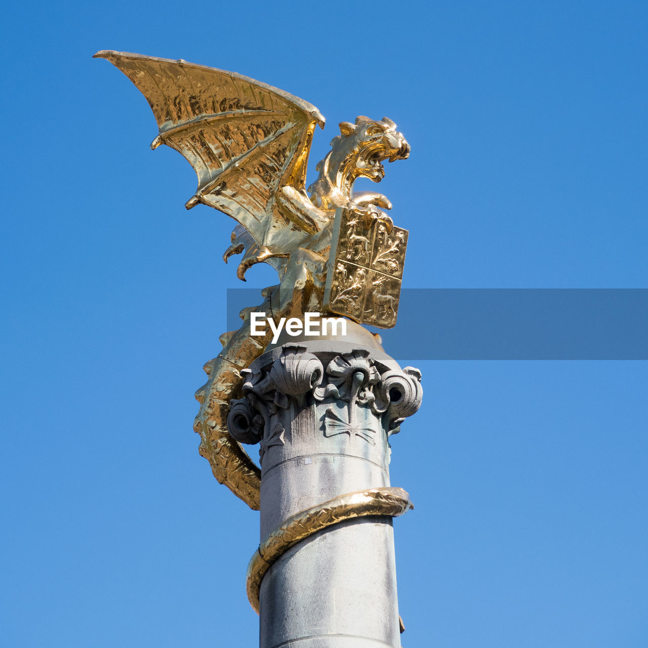 sky, sculpture, low angle view, clear sky, art and craft, architecture, blue, no people, statue, creativity, human representation, representation, day, gold colored, built structure, nature, copy space, religion, female likeness, craft, angel, outdoors, architectural column