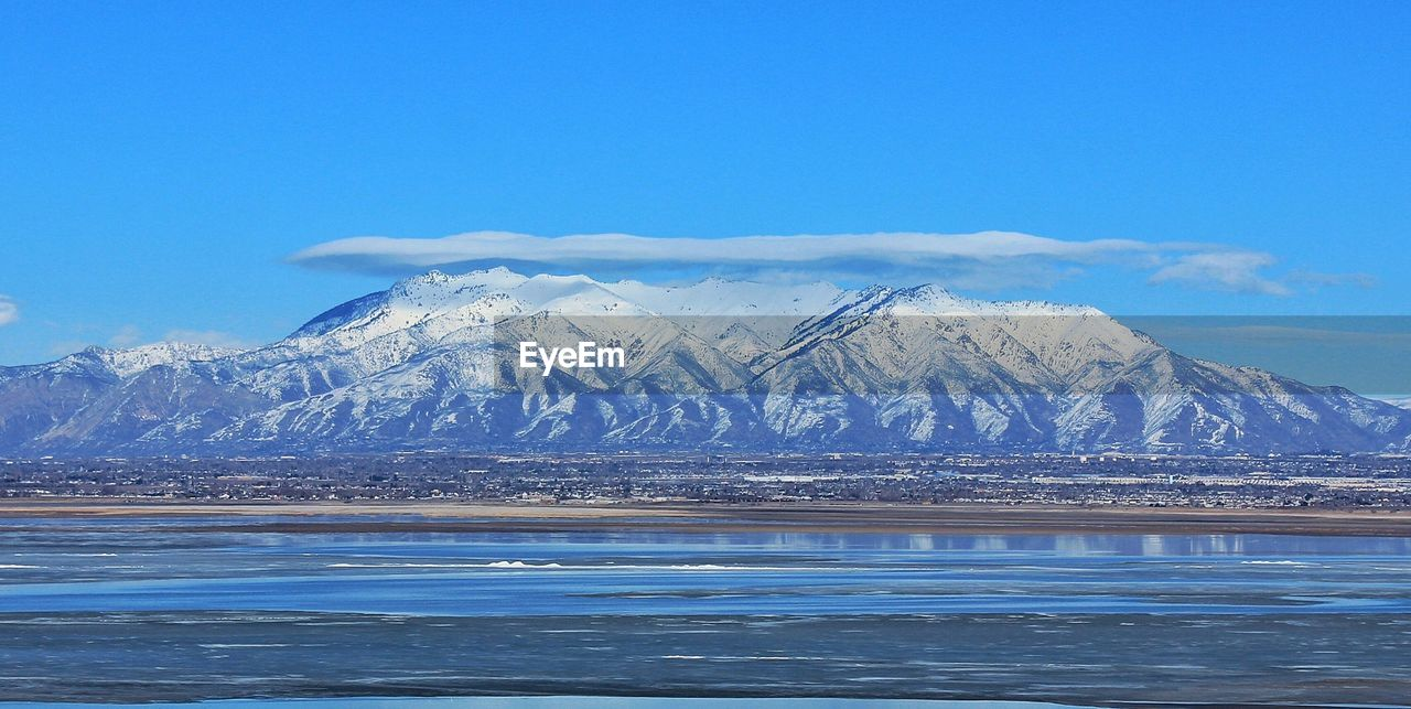 Scenic view of lake and snow covered mountains against sky