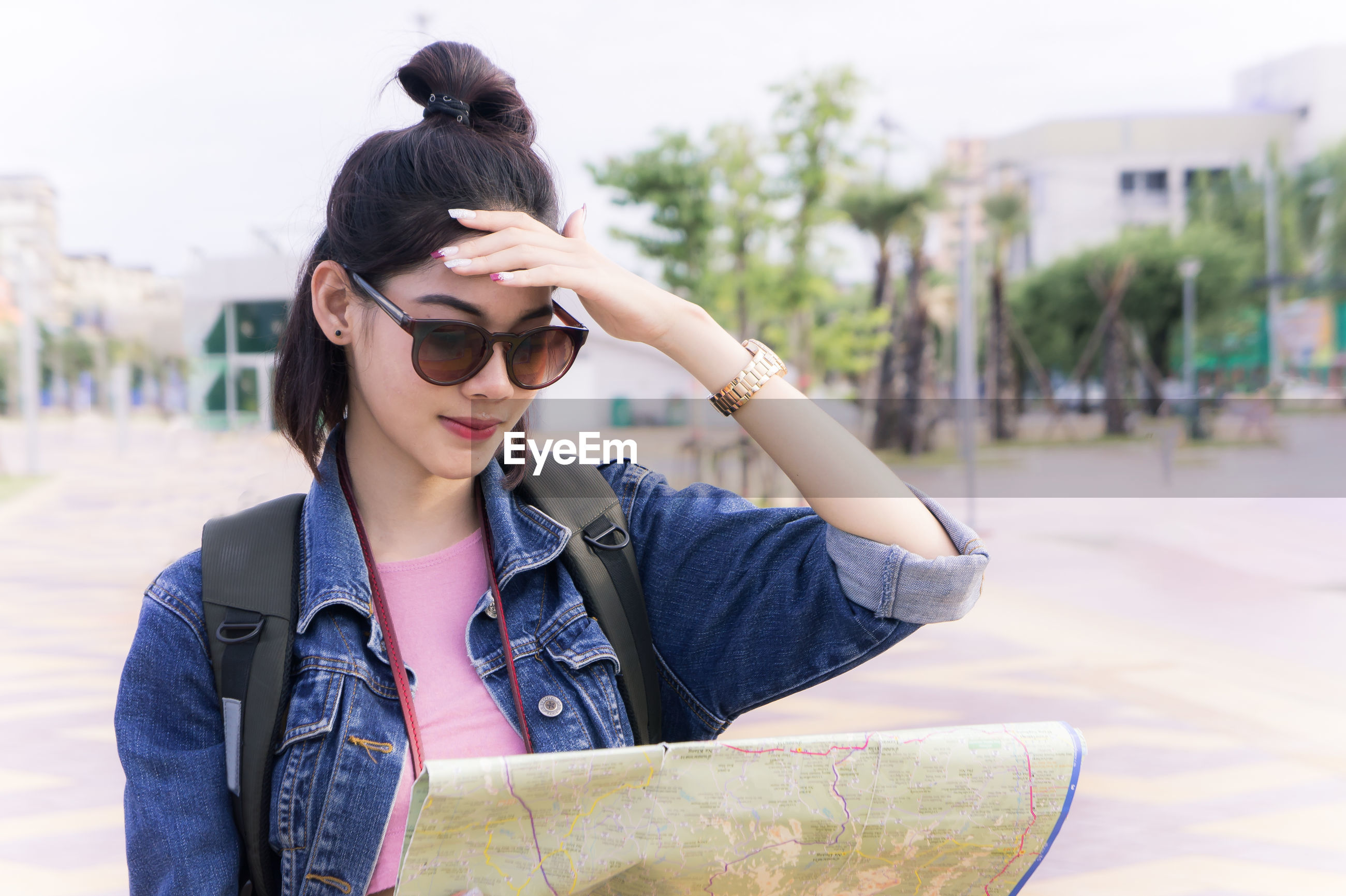 Young woman wearing sunglasses reading map while standing in city