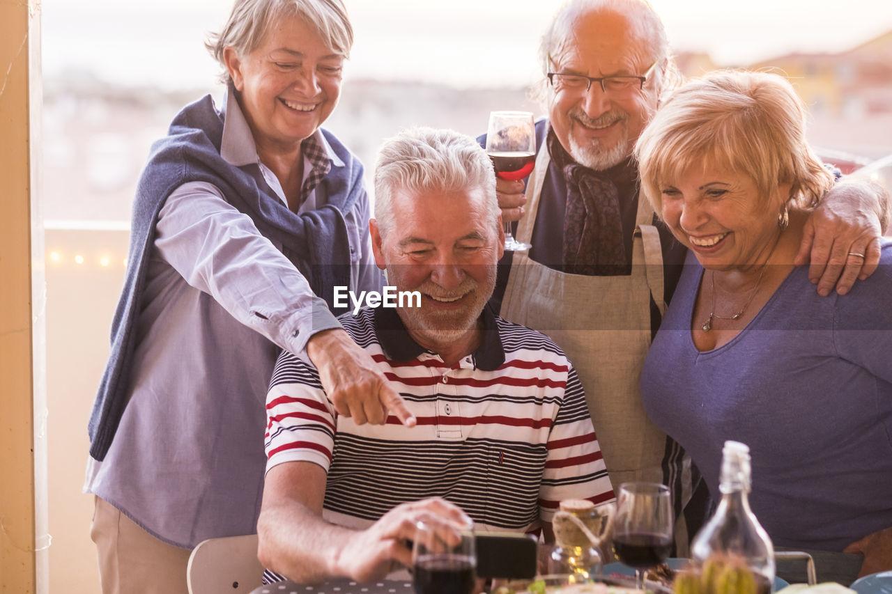 Senior Couple In Balcony During Social Gathering