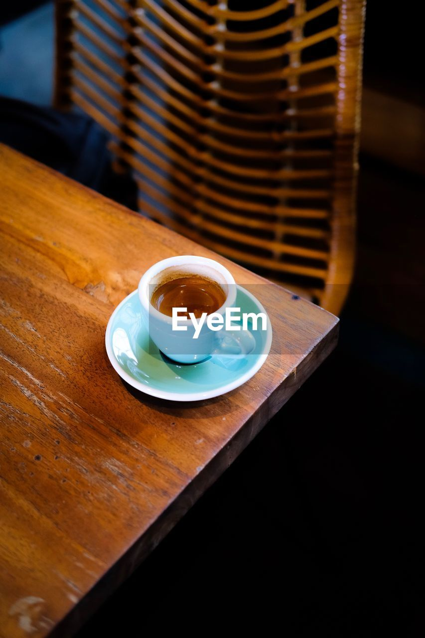 COFFEE CUP ON TABLE AGAINST WOODEN WALL
