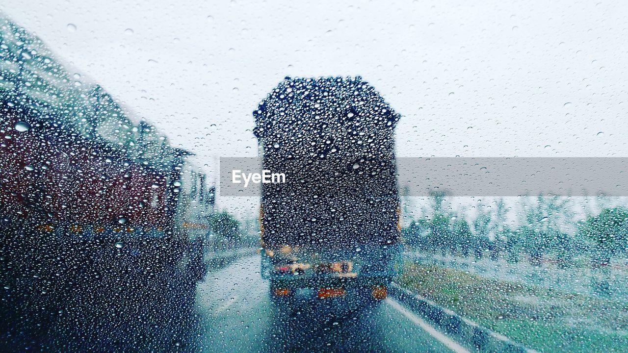 Trucks seen through wet window in rainy season