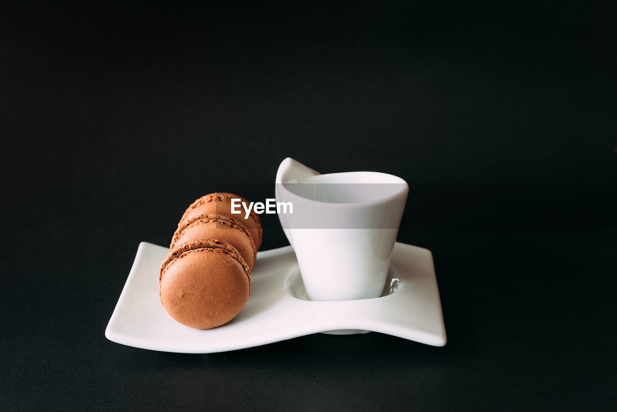 Close-up of coffee cup and macaroons over black background