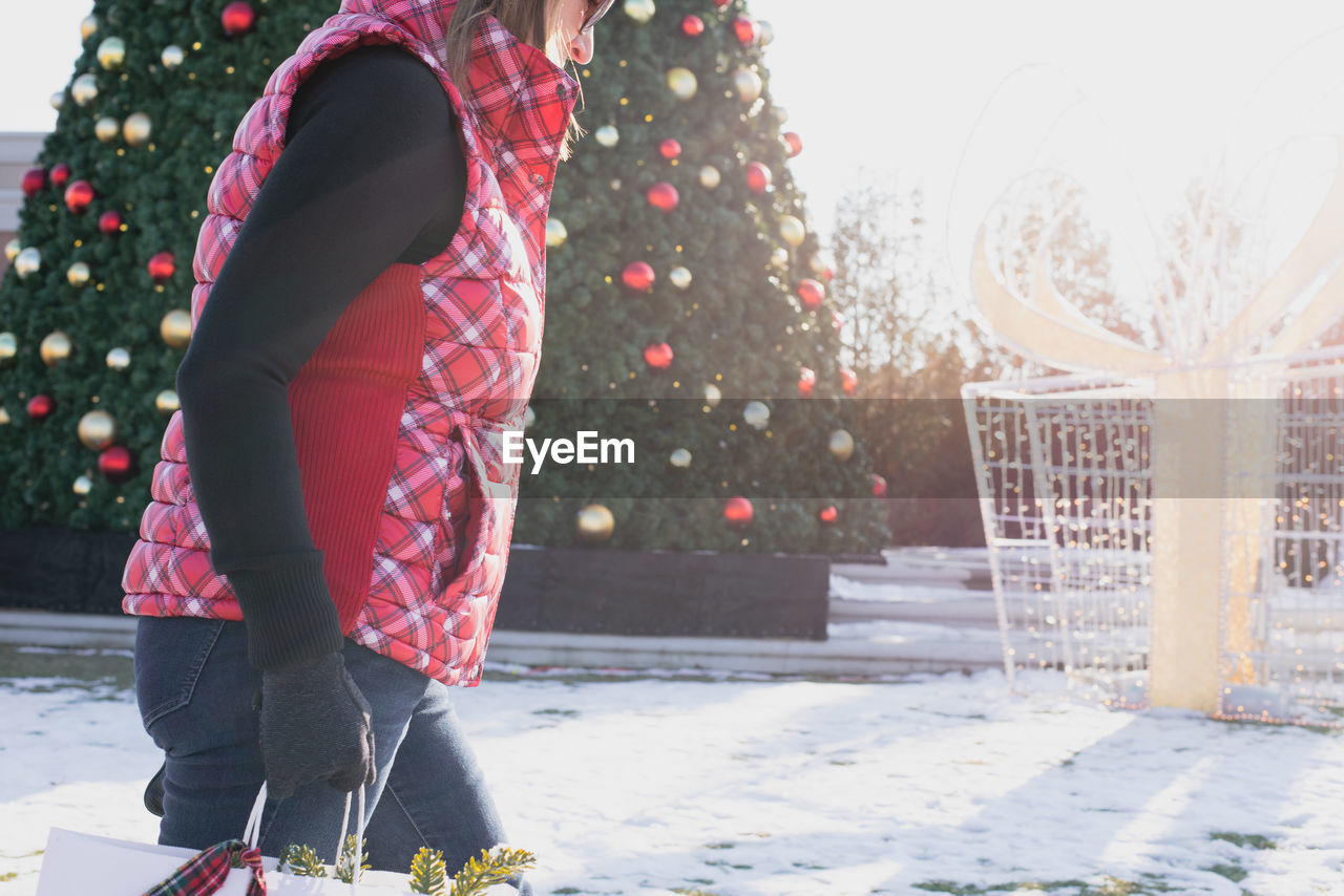 Midsection of woman standing against christmas tree during winter