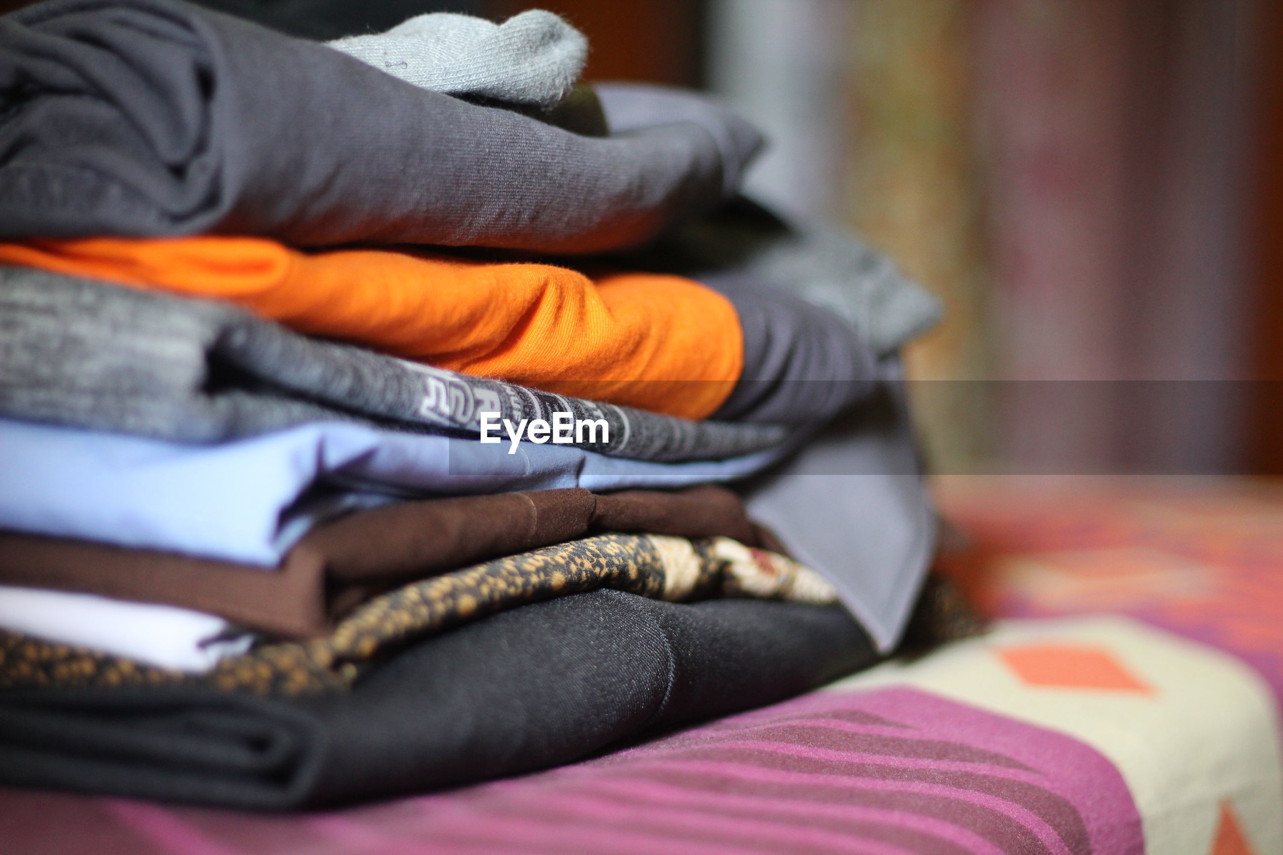 Close-up of clothes stacked on bed at home